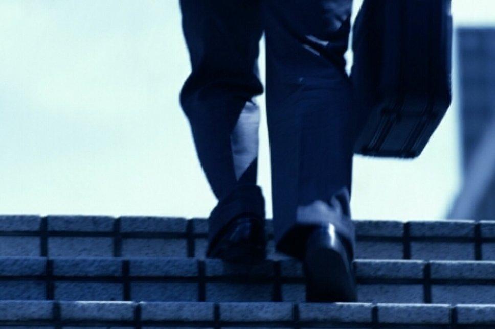 Füße mit Koffer auf Treppe
