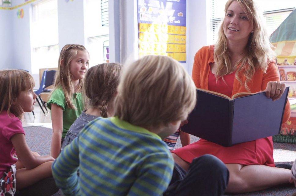 Erzieherin liest Kindern aus Buch