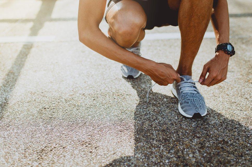 Mann beim Laufen/Schuhe binden