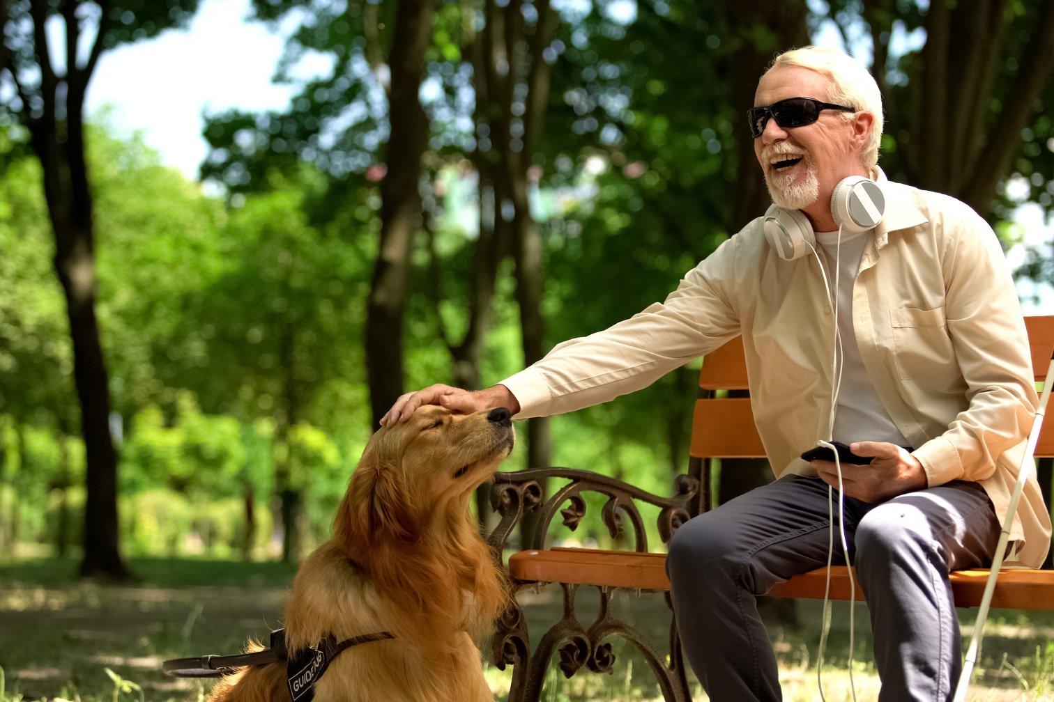Mann mit Sehbehinderung und Assistenzhund