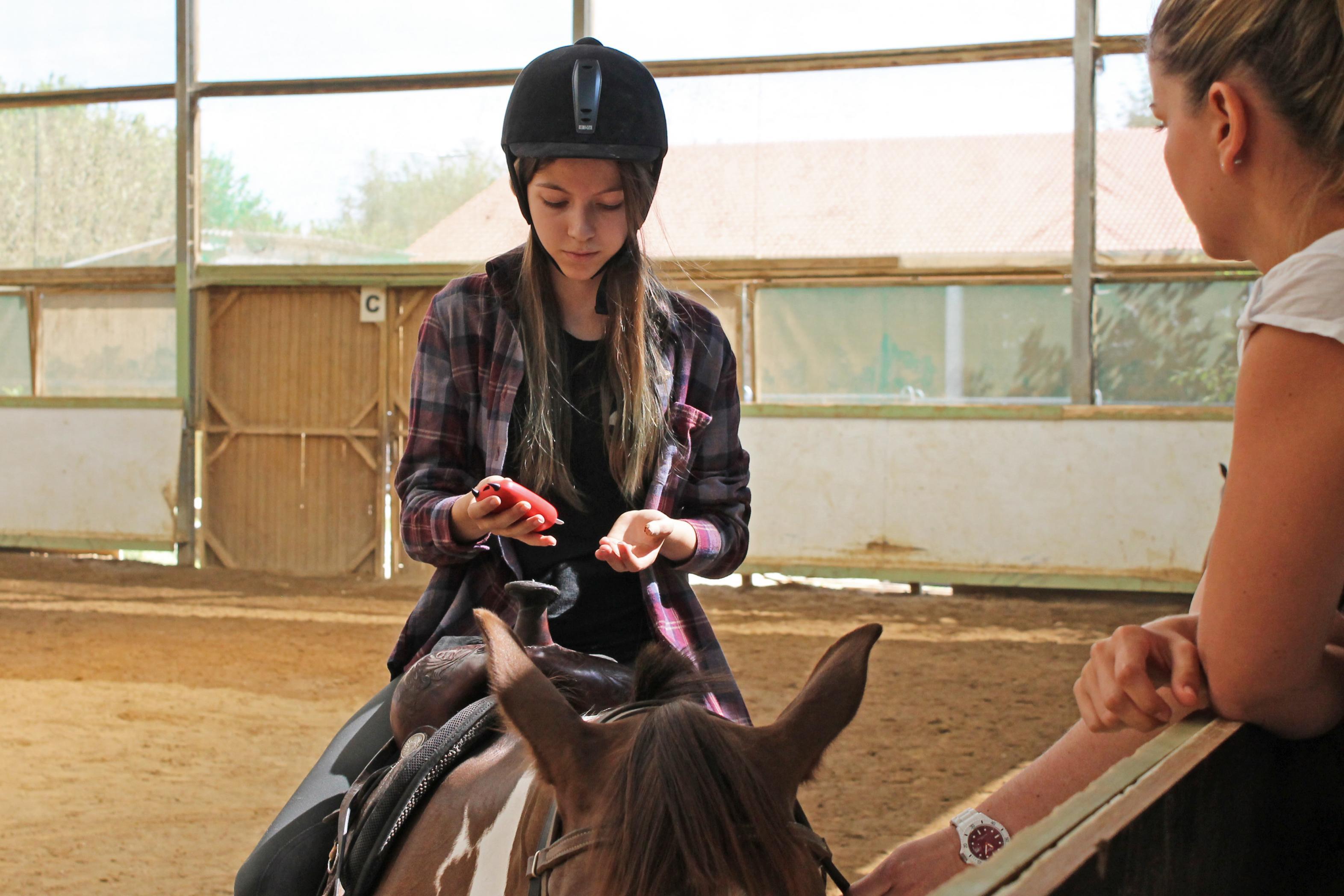 Mädchen auf Pferd mit Messgerät