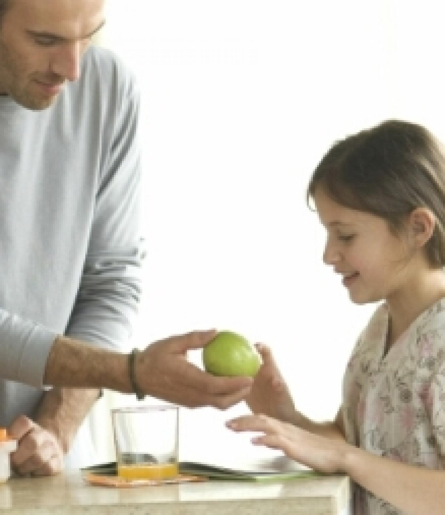 Mann gibt Kind einen Apfel