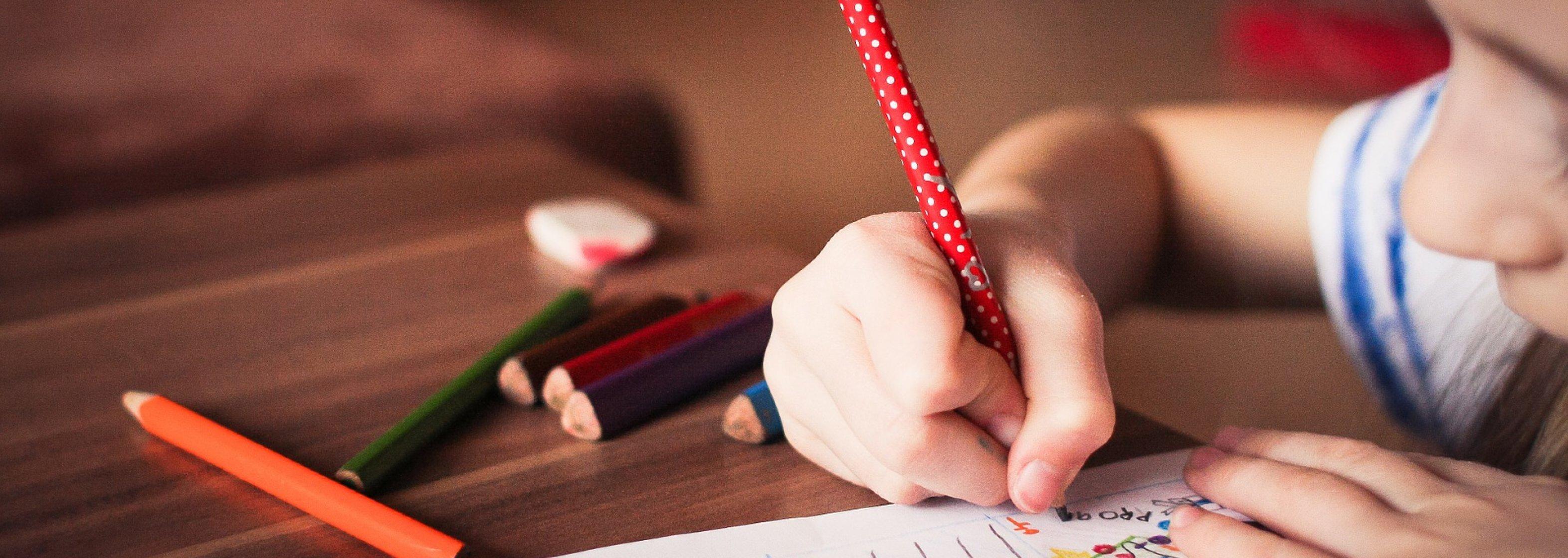 Schule: Kind schreibt mit Stiften