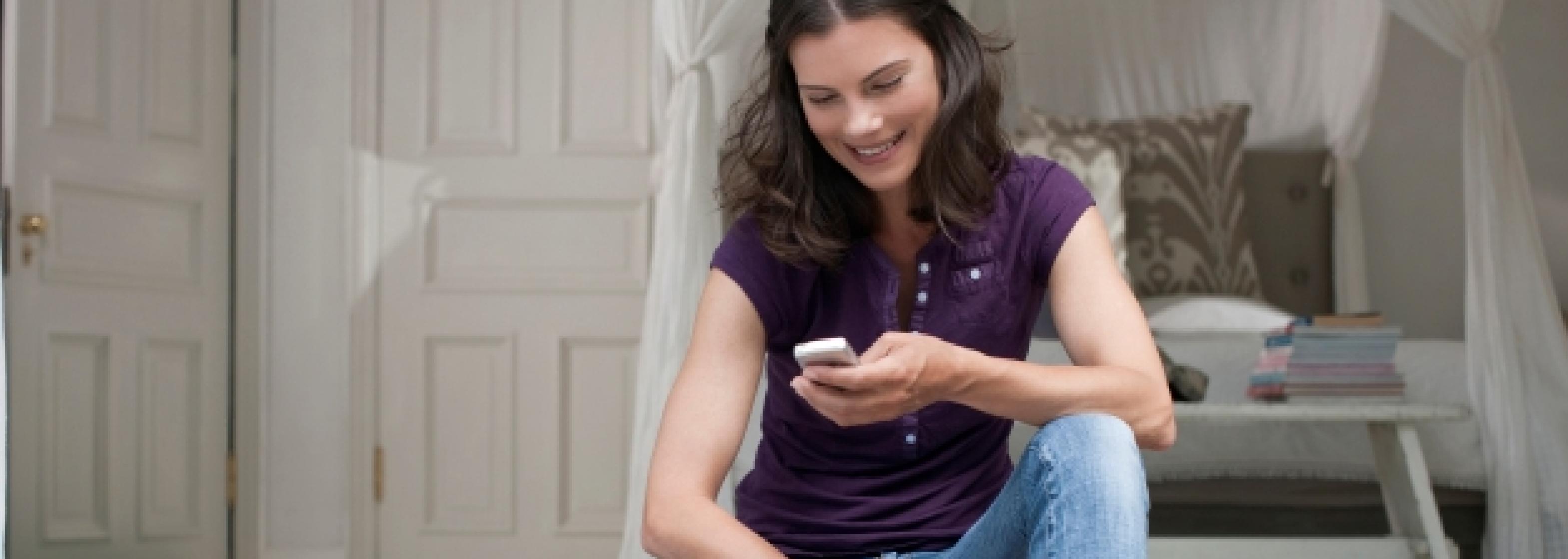 Frau auf Kissen mit Mobielfunkgerät