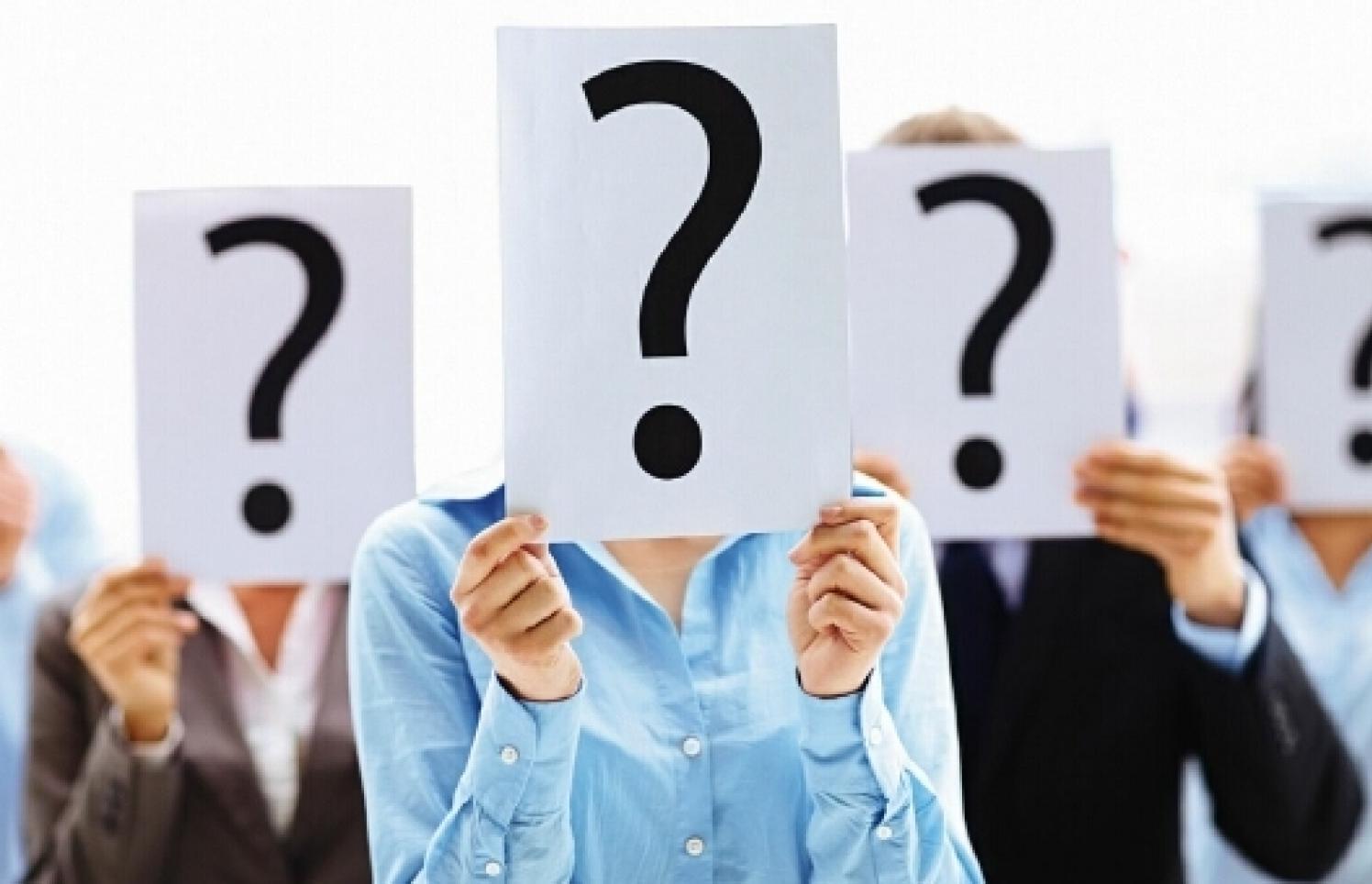 Menschen mit Fragezeichenplakaten